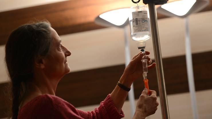 Erika Preisig bereitet für die Flüssigkeitsversorgung eines ihrer Patienten eine Kochsalzlösung (NaCl) vor. (Archiv)