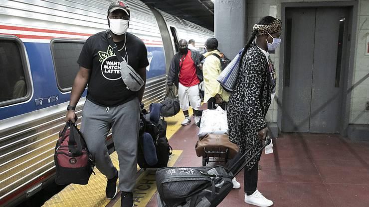 Reisende mit Mundschutz an einem Bahnhof in New York. Foto: Mark Lennihan/AP/dpa