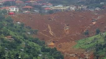 Im Ort Regent in Sierra Leone begräbt eine Schlammlawine Menschen und ganze Häuser.