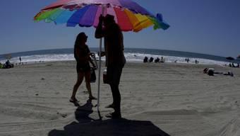 Strandbesucher stellen einen Sonnenschirm auf (Symbolbild)