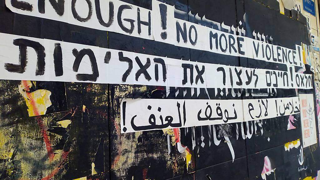 Graffiti gegen die Gewalt zwischen Juden und Arabern an einer Hauswand in englischer, hebräischer und arabischer Sprache. Zwei Rapper haben nach Ausschreitungen im Mai mit einem viral gegangenen Song die wechselseitigen Vorurteile thematisiert. Foto: Eva-Maria Krafczyk/dpa