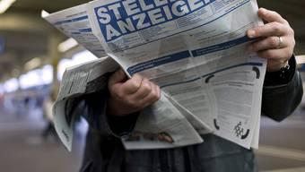 Ein Mann studiert in der Stadt Zürich den Stellenanzeiger (Symbolbild)