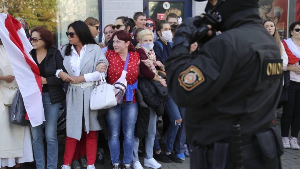 Frauen mit alten belarussischen Nationalflaggen stehen bei einer Demonstration gegen die Wahlergebnisse in Belarus neben einem Polizeibeamten. Foto: Uncredited/TUT.by/dpa