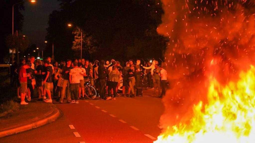 Menschen protestieren auf einer Straße, auf der ein Feuer lodert, gegen die Ankunft hunderter Geflüchteter aus Afghanistan. Die Polizei hat eine Protestaktion, zu der sich rund 250 Menschen in der Nähe des Armeelagers Harskamp (Niederlande, Provinz Gelderland) versammelt hatten, aufgelöst. Foto: -/ANP/dpa