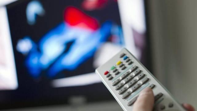 Eine Person bedient eine TV-Fernbedienung (Symbolbild)