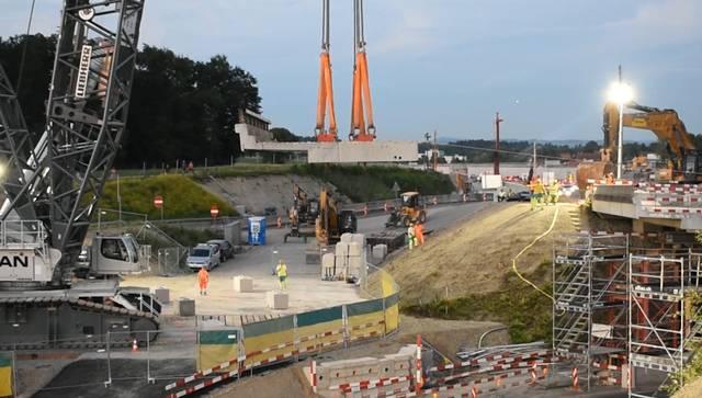Ein Riesenkran baut die Autobahnbrücke über die Wehntalerstrasse zurück. Das Bauwerk wird verbreitert.