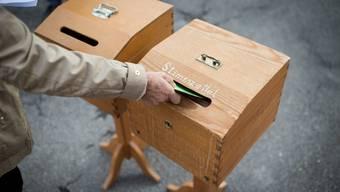Eine Stimmbürgerin wirft die Wahlzettel in die Urne.