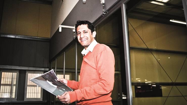 Atif Enver (im Vitis Center in Schlieren) mit einer Abbildung von ihm als Squash-Talent.