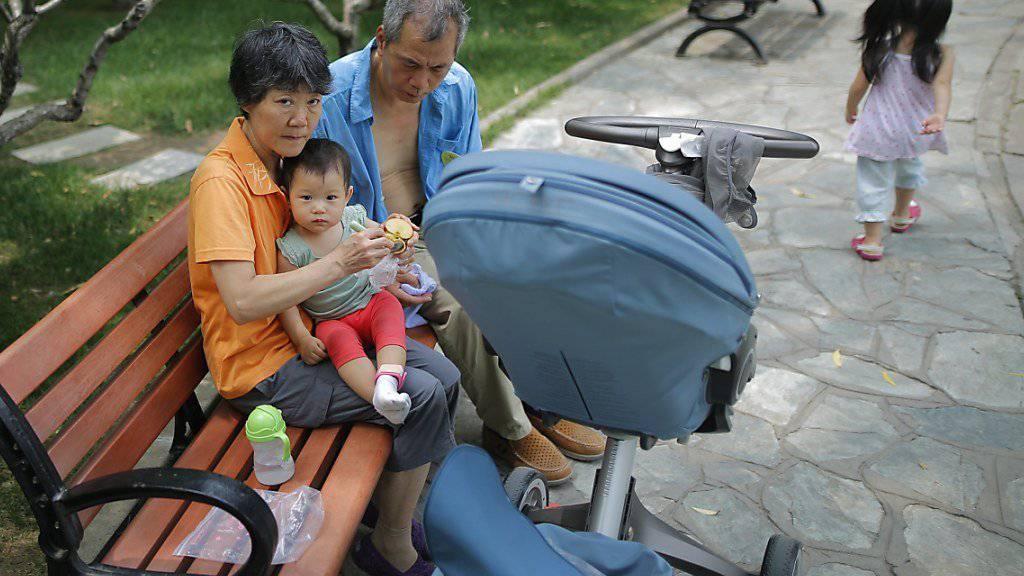 Ein kleines Kind mit älteren Betreuern in einem Park in Peking. (Archivbild)