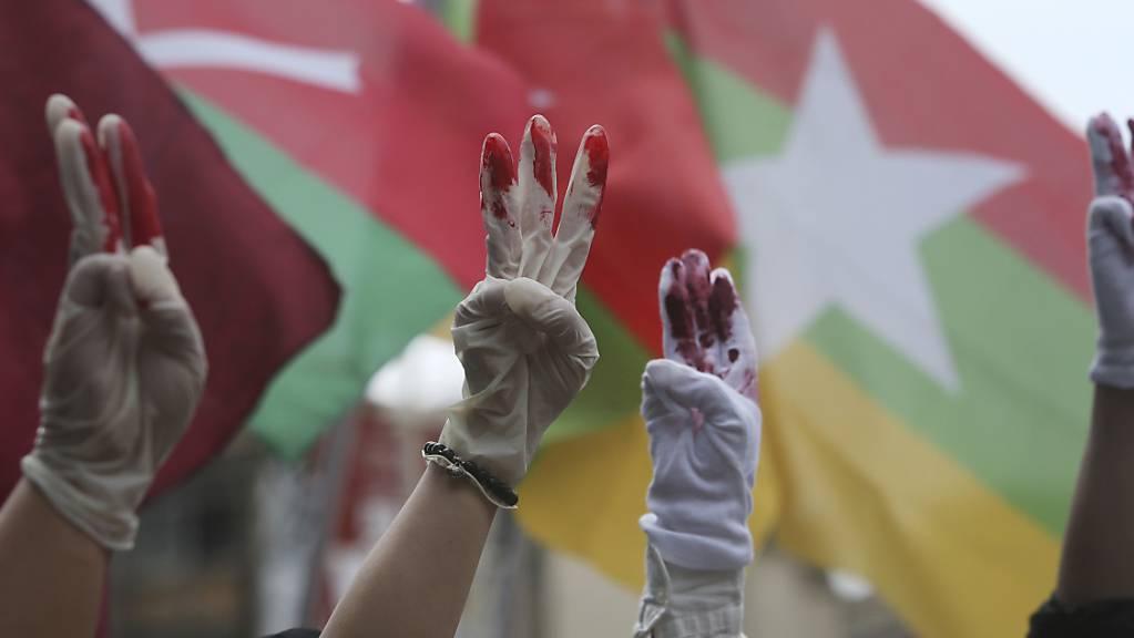 Myanmarische Demonstranten die in Taiwan leben, tragen rot bemalte Handschuhe und zeigen den symbolischen Drei-Finger-GruSS bei einem Protest gegen das Militärregime in Myanmar.(Symbolbild)