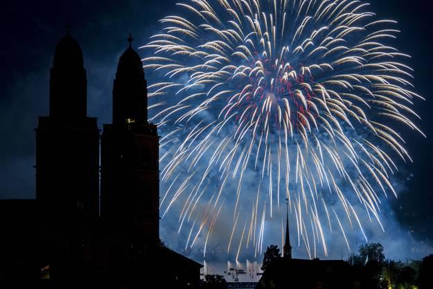 Das erste von drei Feuerwerken am Züri-Fäscht lässt den Himmel über den Kirchtürmen des Grossmünsters und das Seebecken in farbigem Licht erstrahlen.