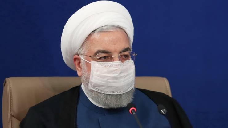 HANDOUT - Hassan Ruhani, Präsident des Iran, leitet eine Kabinettssitzung und trägt dabei eine Maske. Foto: -/Iranian Presidency/dpa - ACHTUNG: Nur zur redaktionellen Verwendung und nur mit vollständiger Nennung des vorstehenden Credits