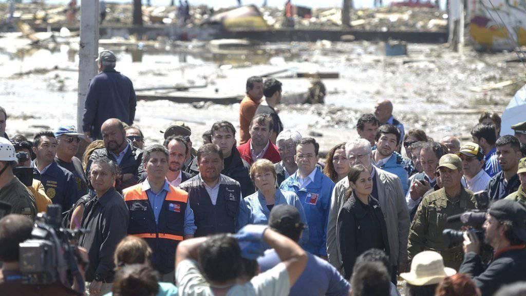 Notstand ausgerufen: Chiles Staatschefin Bachelet (M.) besucht die von Beben und Tsunami betroffene Region Coquimbo.