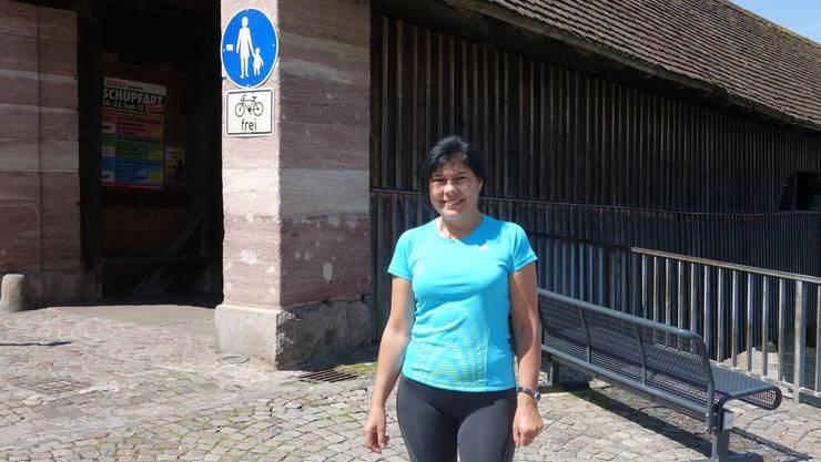 Monika Thoms steht vor der Holzbrücke in der Nähe ihrer Café-Bar mit Vespa-Shop.mw