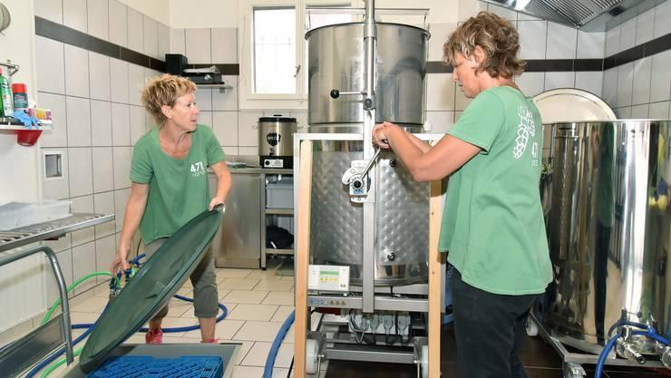 Sabine Eleganti (links) und Linda Winz ziehen das Malz (im oberen Kessel) aus der Bierwürze im unteren Kessel.