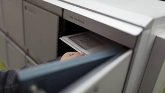 Eine Frau nimmt anlässlich einer Abstimmung die zugeschickten Unterlagen aus dem Briefkasten (Symbolbild)