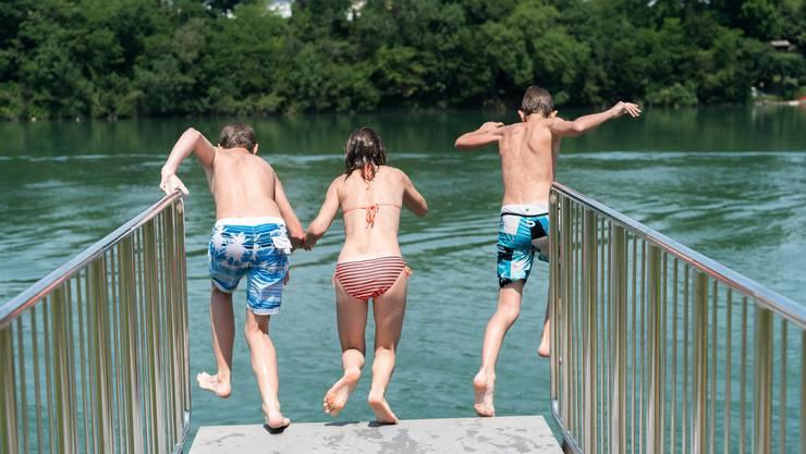 Kinder stürzen sich im Strandbad Rheinfelden in den Rhein. Bald kommt die Abkühlung wieder von oben – in Form von Regen.