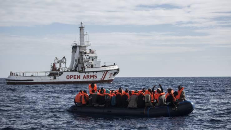"""ARCHIV - Flüchtlinge die auf einem Schlauchboot im Mittelmeer treiben, freuen sich über die Ankunft eines Schiffes der spanischen Nichtregierungsorganisation """"Pro Activa Open Arms"""". Foto: Javier Fergo/AP/dpa"""