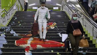 Neu angekommene Reisende mit Mundschutz in der indonesischen Hauptstadt Jakarta. Foto: Achmad Ibrahim/AP/dpa