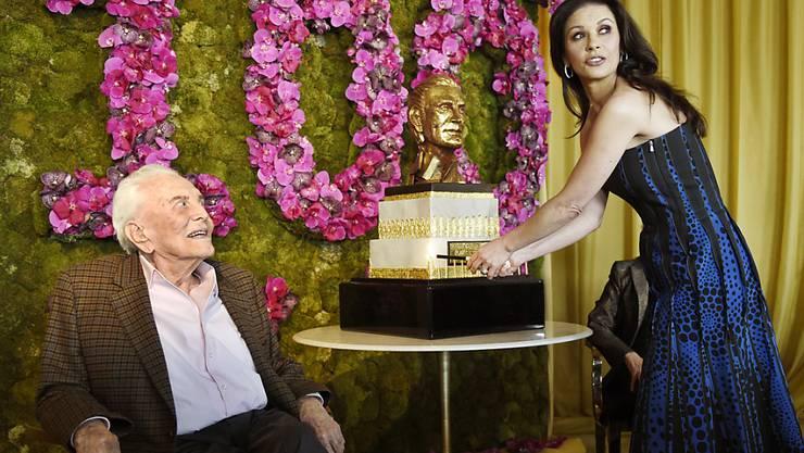 Kirk Douglas sieht zu, wie seine Schwiegertochter Catherine Zeta-Jones die 100 Kerzen auf seiner Geburtstagstorte anzündet.