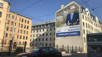 """Ein Wahlplakat der Partei """"Gods kalpot Rigai"""" (Es ist eine Ehre Riga zu dienen) mit einem Porträt des bisherigen Bürgermeisters Olegs Burovs hängt an einer Hauswand in der lettischen Hauptstadt Riga. Foto: Alexander Welscher/dpa"""