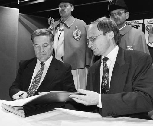 Am 25. Oktober 1993 unterzeichnen im Gymnasium in Laufen Regierungspräsident Werner Spitteler (BL), links, und Regierungs-Vizepräsident Mario Annoni (BE), rechts, die Verwaltungsvereinbarungen zwischen den Kantonen Bern und Basel-Landschaft.