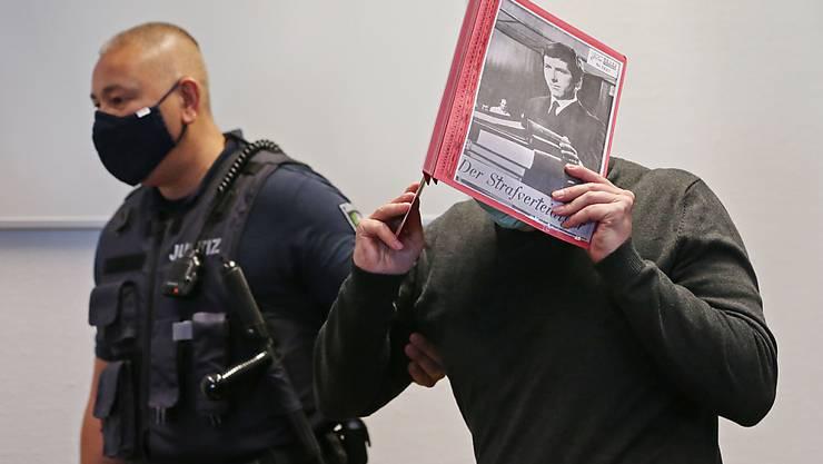 """dpatopbilder - ARCHIV - Der Angeklagte (r) im Prozess wegen schweren sexuellen Missbrauchs von Kindern wird von einem Justizbeamten in den Gerichtssaal geführt, während er sich eine Mappe mit aufgeklebten Fotos von Filmszenen des Films """"Der Strafverteidiger"""" vor das Gesicht hält. Foto: Oliver Berg/dpa - ACHTUNG: Nur zur redaktionellen Verwendung im Zusammenhang mit einer Berichterstattung über den Prozess im Missbrauchsfall Bergisch Gladbach und nur mit vollständiger Nennung des vorstehenden Credits"""