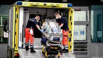 Sanitäter vom Bundeswehr Rettungsdienst bringen die Spezialtrage, mit der Nawalny in die Charite eingeliefert wurde, zurück in den Krankenwagen. Foto: Kay Nietfeld/dpa