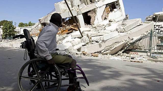 Ein Verletzter vor einem eingestürzten Haus