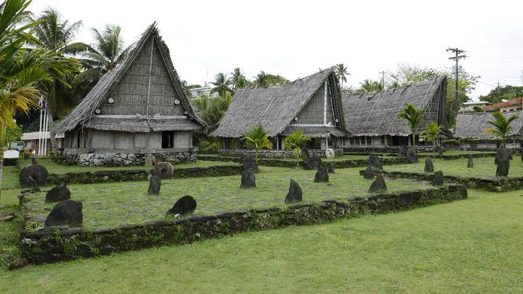 Traditionelle Häuser auf Yap. Auch zu sehen: Das runde Steingeld. Hierher hat es das Coronavirus noch nicht geschafft.