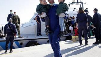 Ein Helfer mit zwei geretteten Kindern auf Kreta