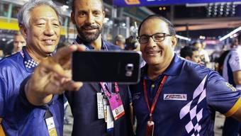 Rio Ferdinand (Mitte) macht in Singapur ein Selfie mit Premierminister Teo Chee Hean (l) und dem Minister für Handel und Industrie (r)