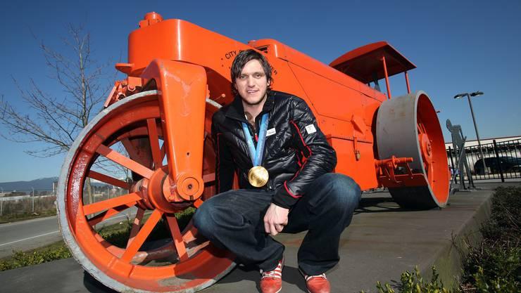 Mike Schmid posiert in Canvouver vor einer Strassenmaschine. im Sommer ist der Skicross-Crack in seinem beruf als Strassenbauer tätig. (Bild: Sven Thomann/Blick)
