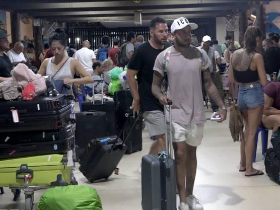 Touristen versuchen auf dem Flughafen von Ko Samui, dem Tropensturm Pabuk noch rechtzeitig zu entrinnen.