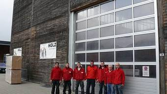 Geschäftsleitungsmitglied Beat Peterhans, umrahmt von 6 von insgesamt 35 Angestellten, vor der prämierten Produktionshalle an der Fislisbacher Bernardastrasse