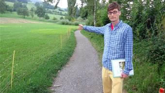 Projektleiter Erik Olbrecht steht vor dem Uferwegabschnitt, der abgetragen wird, und deutet aufs Areal der Flachwasserbucht. tf