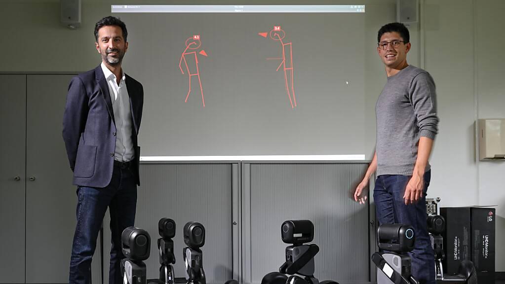 Laborleiter Alexandre Alahi (links) und Doktorand Lorenzo Bertoni (rechts) im Visual Intelligence for Transportation Laboratory an der ETH Lausanne EPFL. Auf der Leinwand hinter ihnen Strichmännchen, zu denen die Abstands-Analysanden umgewandelt werden  (Alain Herzog / 2021 EPFL).