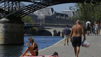 Menschen genießen das sonnige Wetter am Pariser Seineufer. Im Kampf gegen das Coronavirus gilt nun auch in Paris eine Maskenpflicht an zahlreichen öffentlichen Orten im Freien. Foto: Michel Euler/AP/dpa