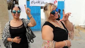 Zwei Frauen vor einem Wahllokal in Tunis mit tintengefärbtem Zeigefinger - der Beleg, dass sie an den Präsidentenwahlen teilnahmen.