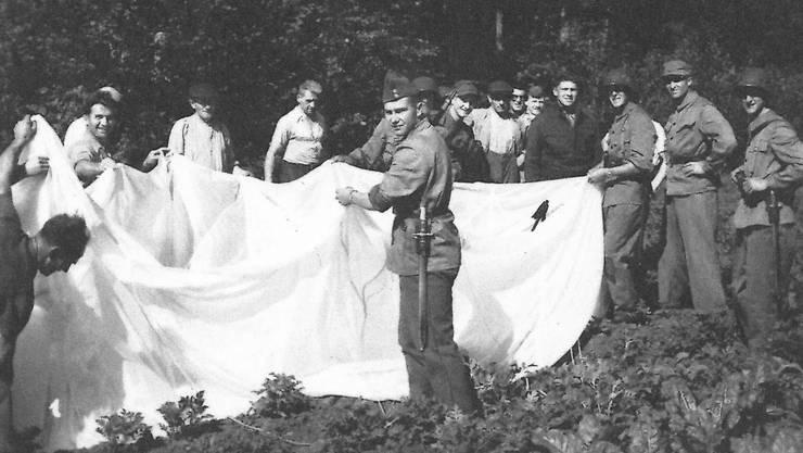 Beim Schiessstand Gerlafingen abgesprungen: Ein Besatzungsmitglied des B-24 (Pfeil) samt seinem Fall schirm und einheimischen Zaungästen.