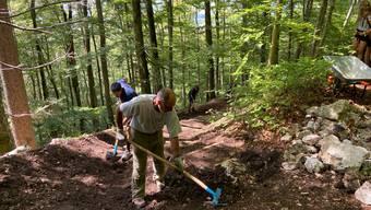Wanderer und Biker beim gemeinsamen Instandhalten eines Wanderweges beim Weissenstein.