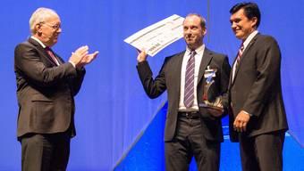 Die Preisübergabe erfolgte in der St.Jakob-Halle. Von links nach rechts: Bundesrat Johann Schneider-Ammann, Preisgewinner Michel Manz, Direktor Wirtschaftskammer Baselland Christoph Buser.