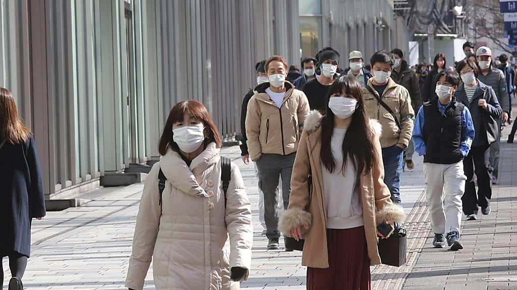 Passanten tragen Schutzmasken und gehen einen Bürgersteig in Tokio entlang. Foto: Koji Sasahara/AP/dpa