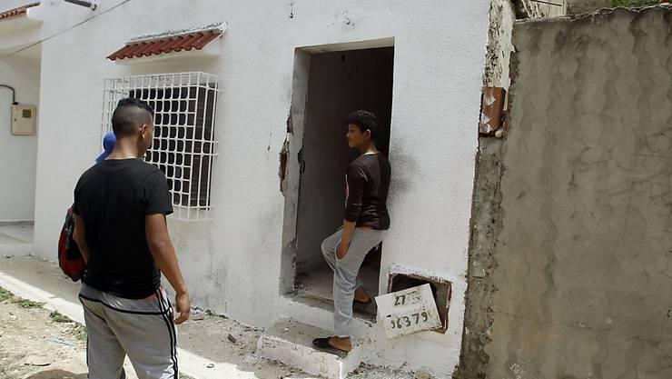 Anwohner versammeln sich bei einem Haus in Tunis, in dem Eliteeinheiten der tunesischen Polizei zwei mutmassliche Terroristen töteten. Die Polizei fand Waffen und Munition.
