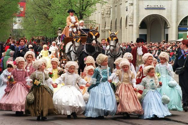 Die Kinder und Zünfte laufen in historischen Kostümen, Trachten und Uniformen mit.