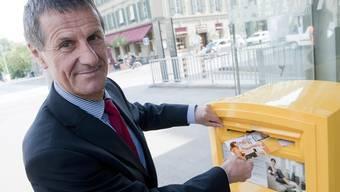 Post-Konzernleiter Jürg Bucher wirft in Bern eine Karte in einen Briefkasten. (Archiv)
