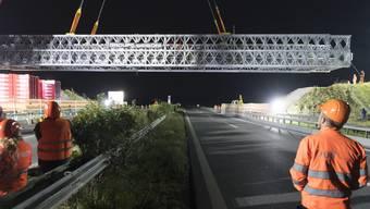 Mit dem grössten Kran der Schweiz haben Bauarbeiter in der Nacht auf auf Dienstag eine Autobahnbrücke über der A1 zwischen Lausanne und Genf ersetzt.
