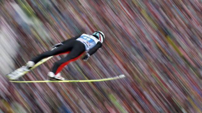 Ein Rauschen im Wind: Während Simon Ammann in den Hexenkessel von Innsbruck fliegt, lassen sich die 22 000 Zuschauer im Hintergrund nur erahnen. Foto: Matthias Schrader/Keystone