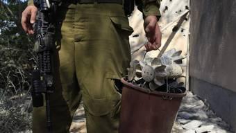 Ein israelischer Soldat sammelt abgefeuerte Mörsergranaten ein