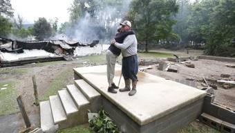 Ein Paar umarmt sich auf den Resten seines Hauses in White Sulphur Springs im US-Bundesstaat West Virginia.